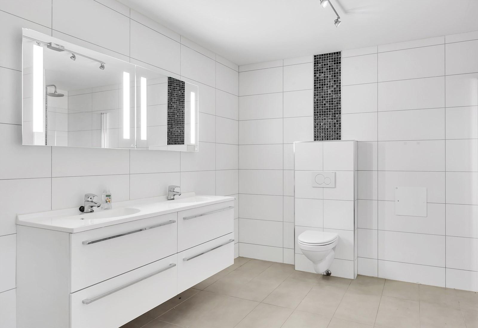 Badet er flislagt på vegger og gulv. Vegghengt toalett. Stor innredning med dobbelvask. Dusjing i dusjnisje.
