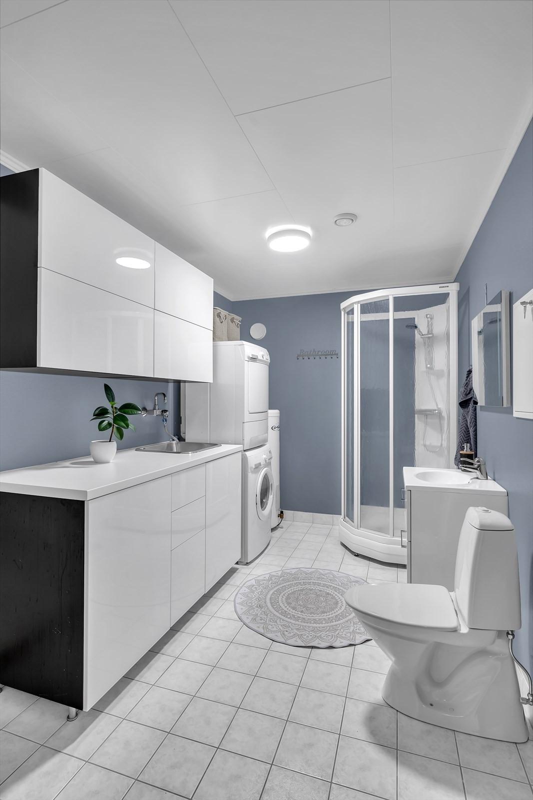 Vaskerommet har godt med innredning, dusjkabinett og flis på gulv med gulvvarme