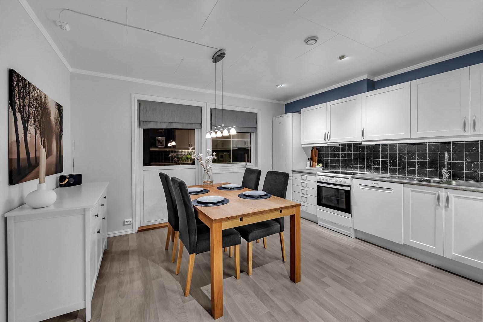 Stort kjøkken med plass til stort spisebord inne på rommet. Utgang til markterrasse.