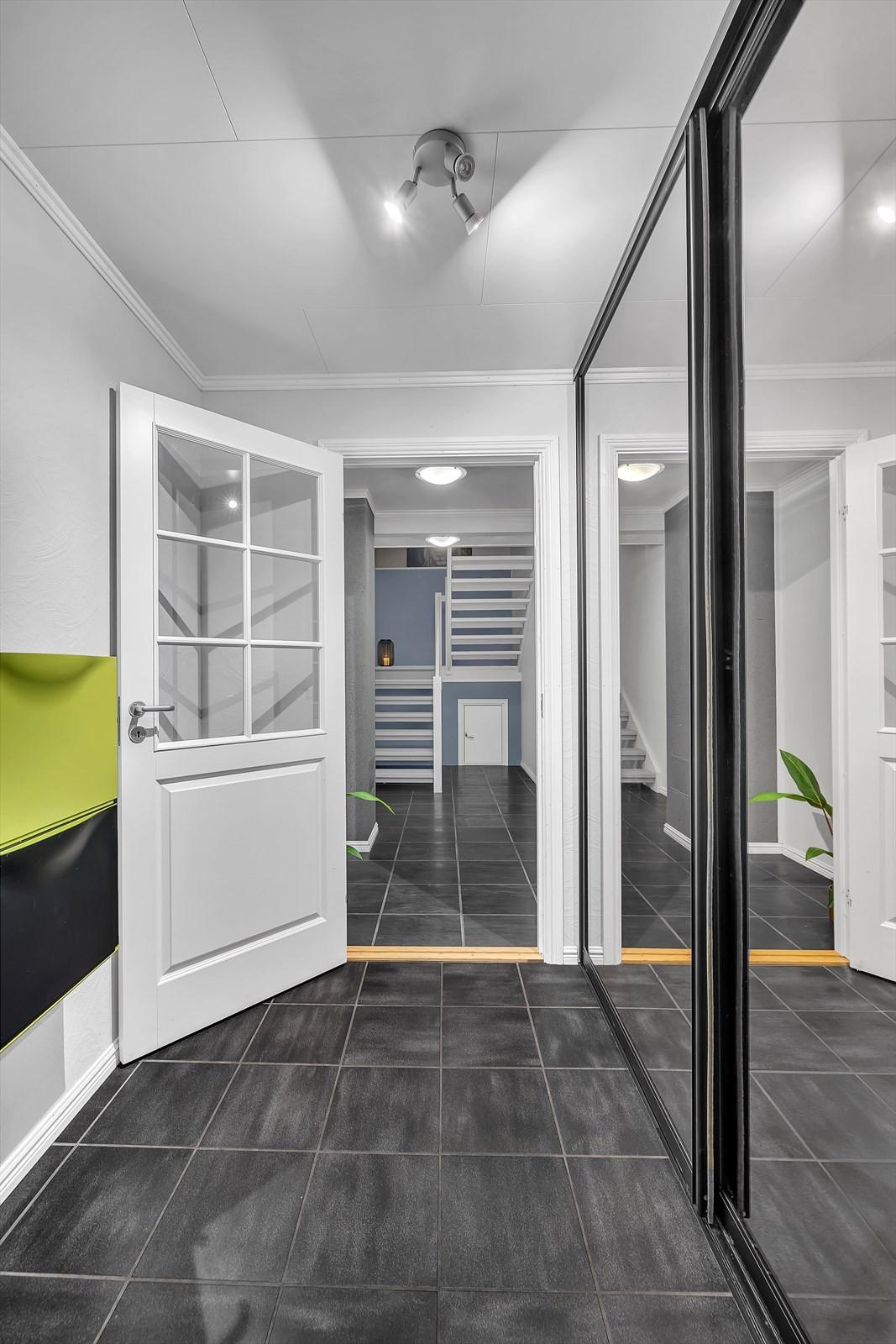 Gang med fliser med gulvvarme og stor garderobe med speilfronter
