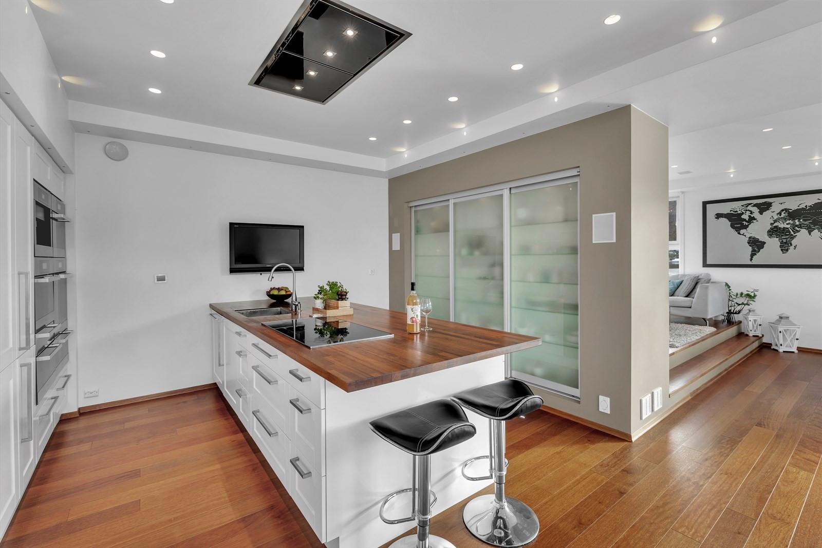 Meget tiltalende kjøkken med integrerte hvitevarer som varmeskuffer for fat og deler til ovn, dampovn, kombinert ovn og vanlig ovn. Kjøleskap med fryser, vinskap og kaffemaskin.