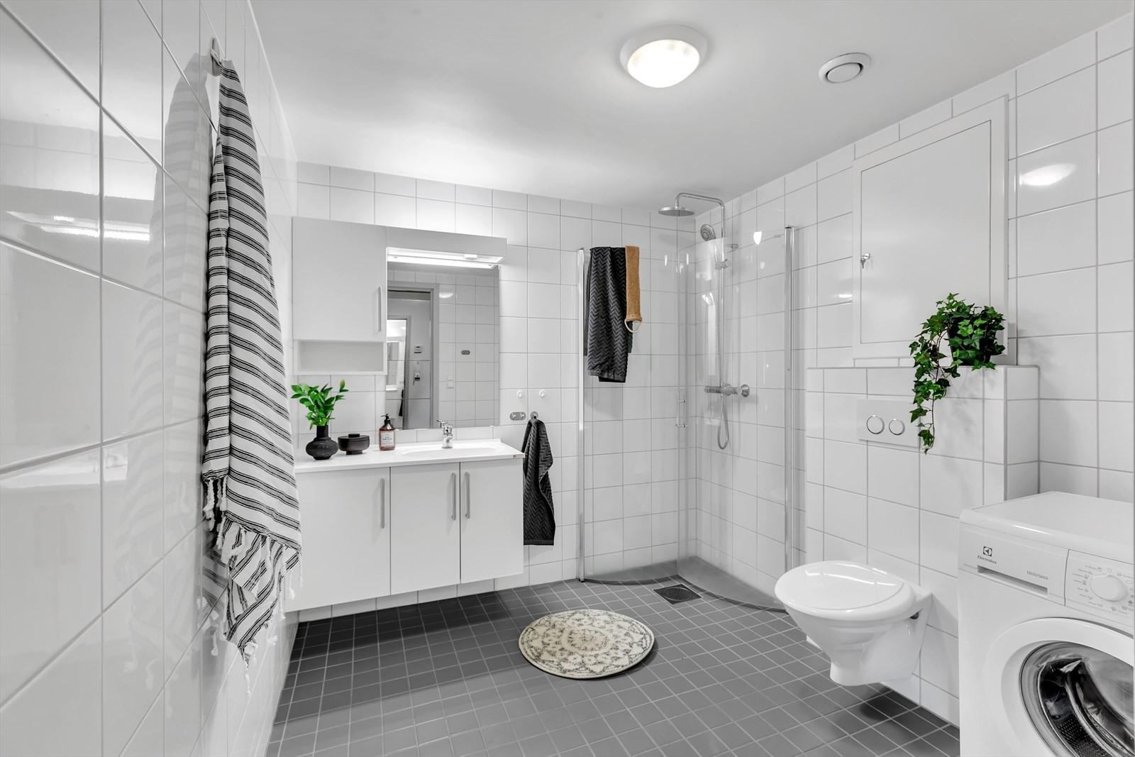 Romslig og komplett flislagt bad. Vegghengt toalett og dusjhjørne.