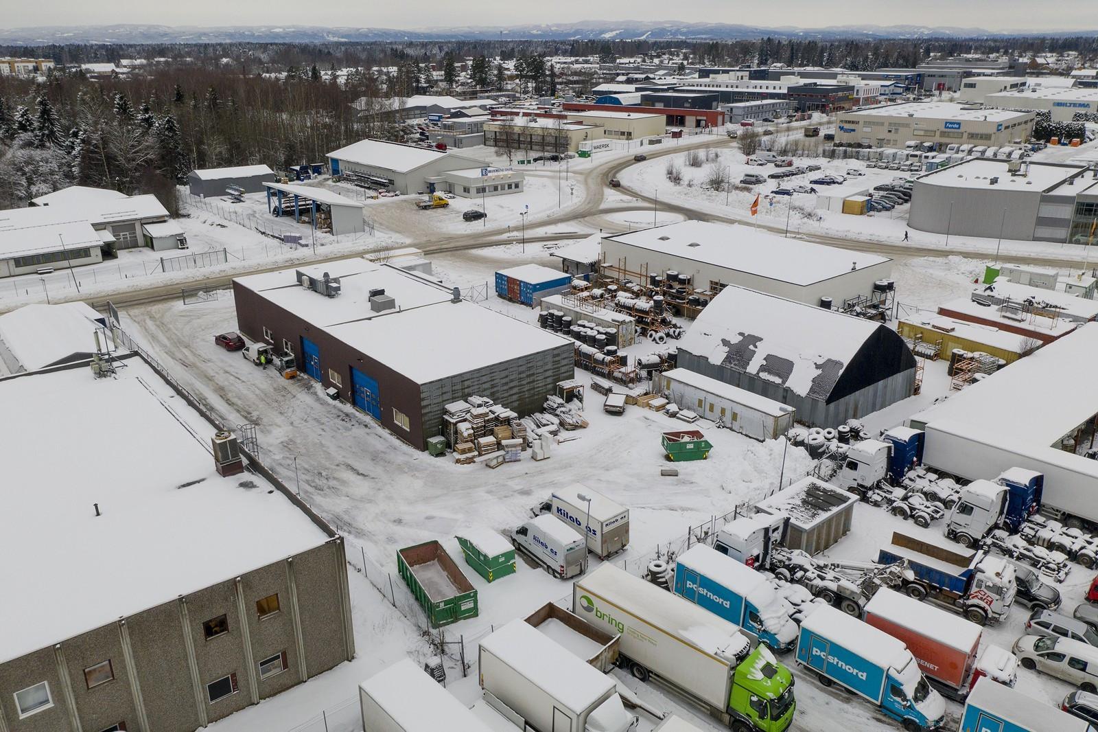 Inngjerdet tom med asfaltert kjøre- og parkeringsareal. Gruset plass bak bygget for oppstilling og lagring.