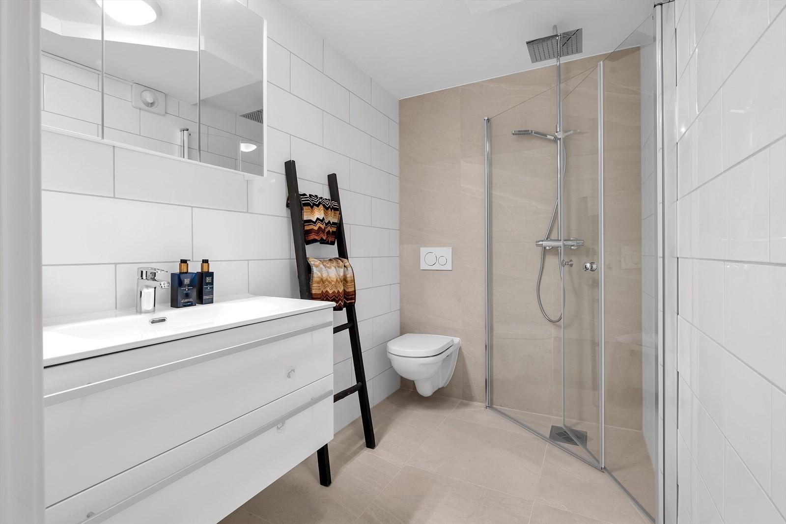 Badet er nyetablert og er flislagt. Vegghengt WC. Innslagbare dusjdører. Stor baderomsinnredning.