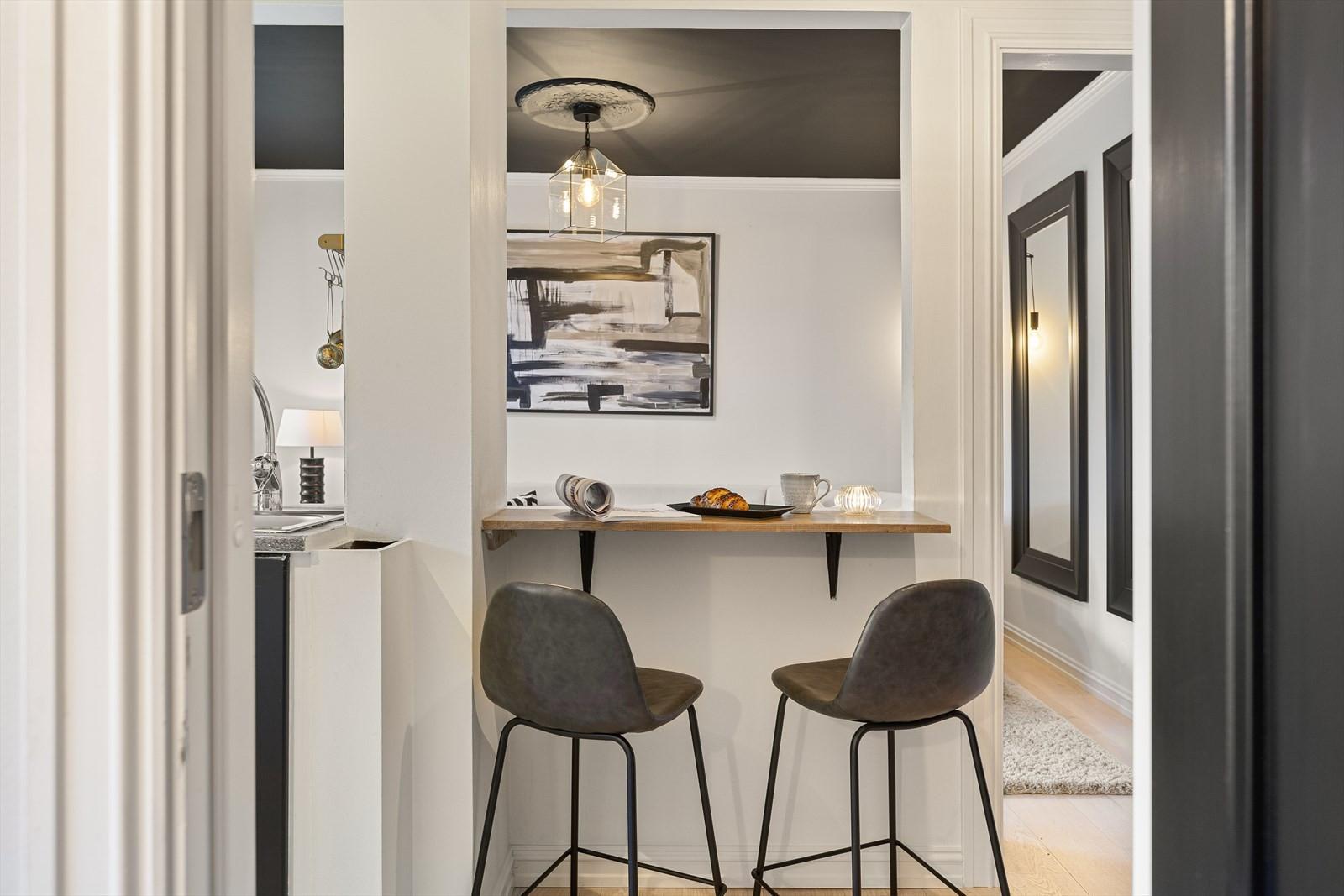 Delvis åpning i vegg skaper en naturlig avdelt sone mellom stue og kjøkken.