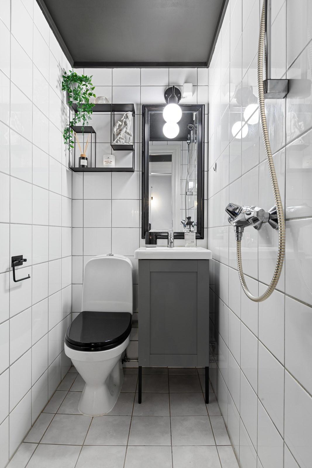 Komplett flislagt bad med mørke detaljer. Ny servant og baderomsinnredning fra 2021. Varmekabler i gulv.