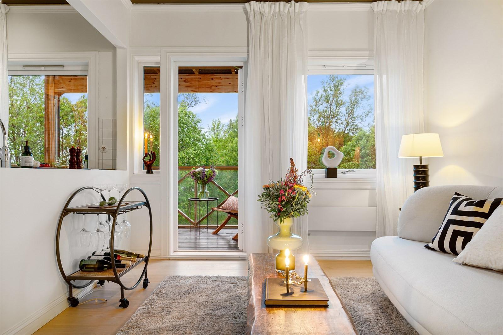 Mange vindusflater slipper inn rikelige mengder med naturlig lys i rommet og gjør at utsikten kan nytes også inne i leiligheten.