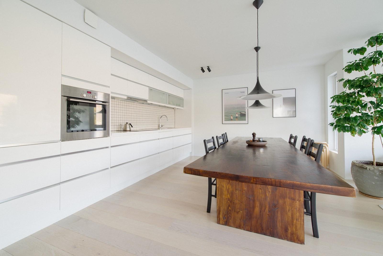 Moderne og pen innredning med skjulte gripelister og fliser over kjøkkenbenk