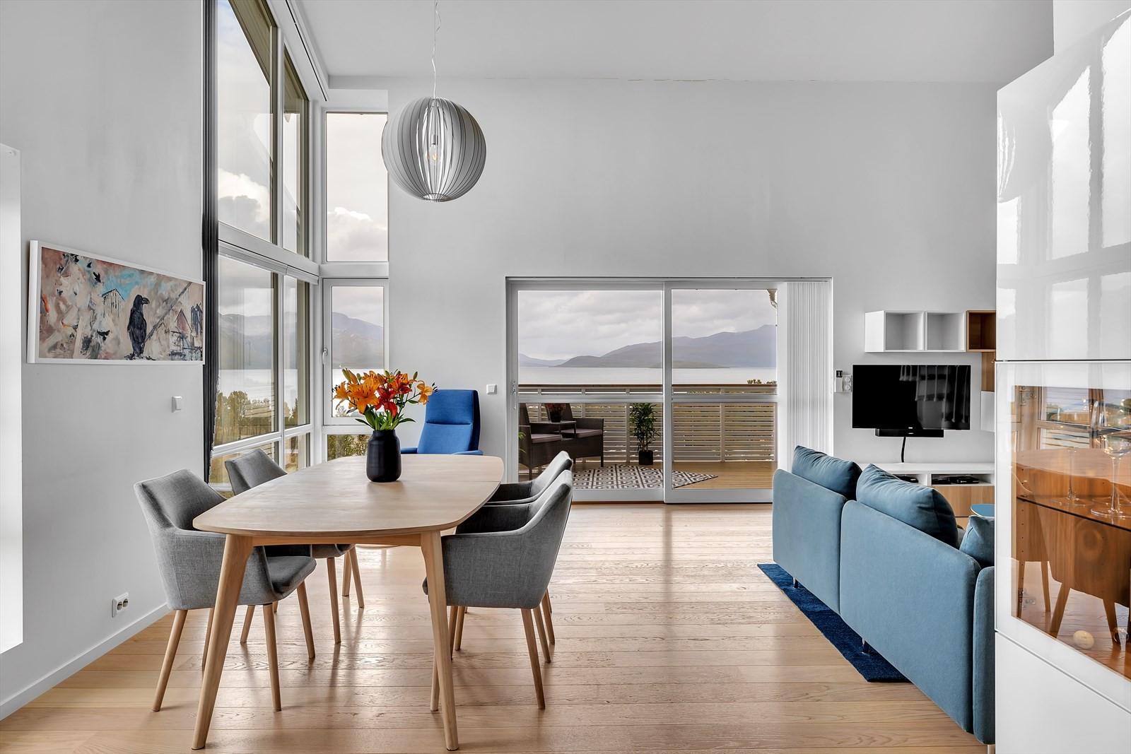 Stue og kjøkken i åpen løsning. Rommet har svært god takhøyde og store vindusflater. Skyvedør  ut til balkong.