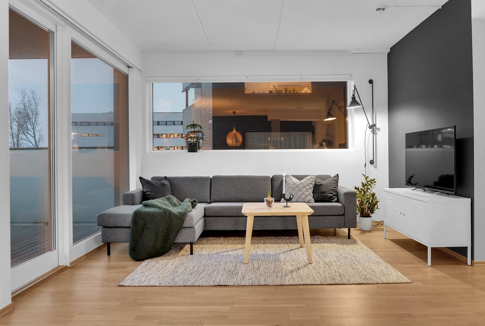 Stue med store vindusflater og skyvedør ut til terrassen.