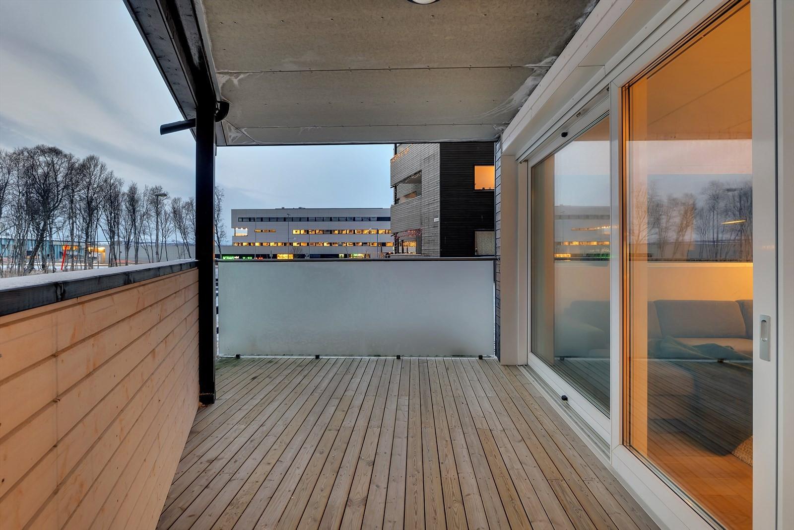 Romslig, takoverbygd terrasse med skyvedør fra stue.