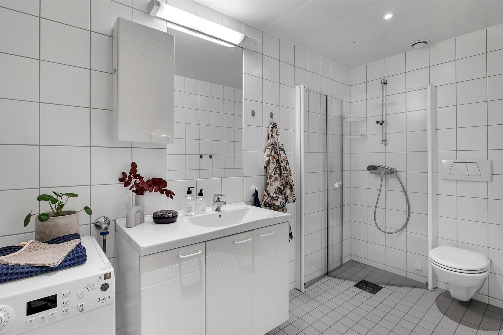 Badrom med vegghengt toalett og dusjvegger.