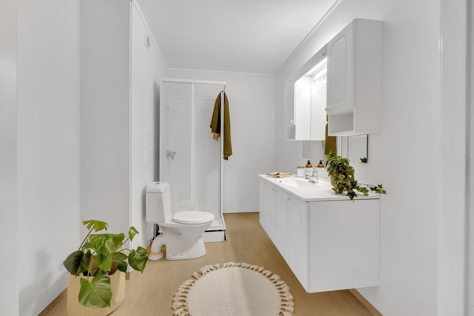 Lyst og trivelig bad med dusjkabinett, wc, servant og baderomsinnredning med over/underskap.