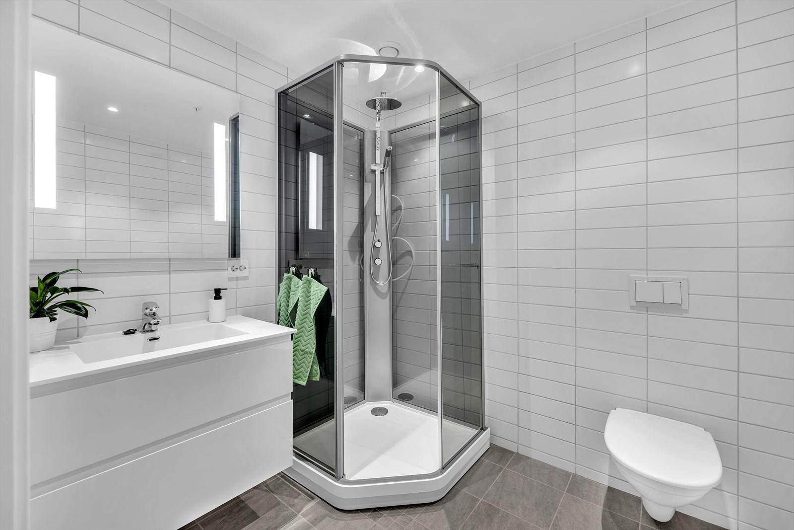Badet er praktisk og fint med fliser på gulv og vegger