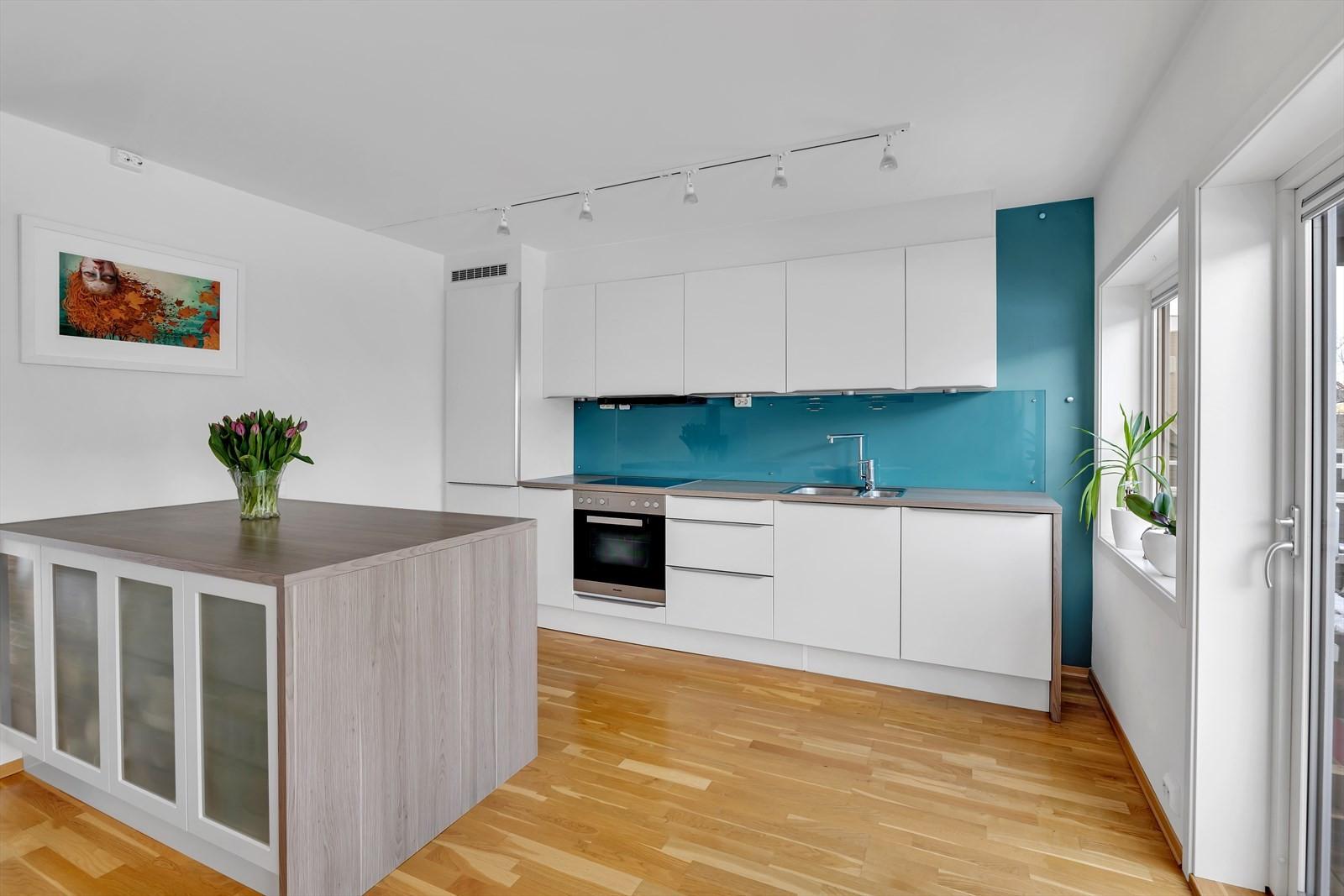 Kjøkken med integrerte hvitevarer og kjøkkenøy med skapinnredning