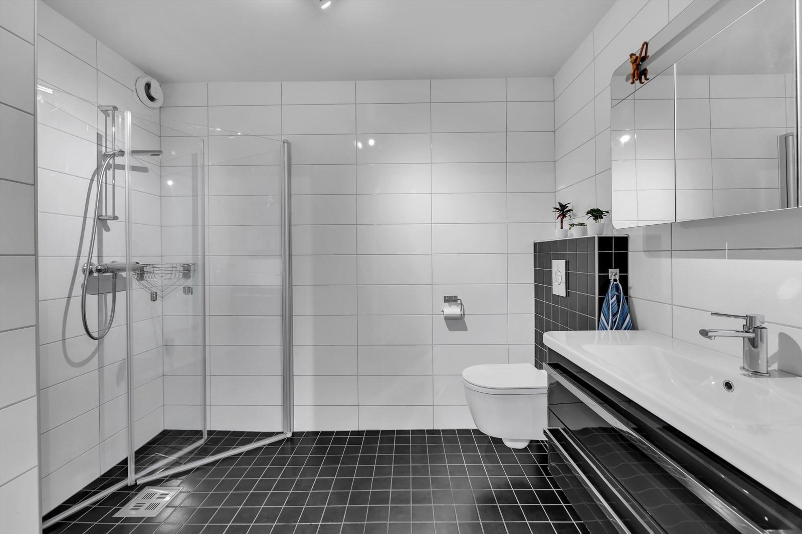 Flislagt bad med dusjhjørne og vegghengt wc. Moderne innredning.