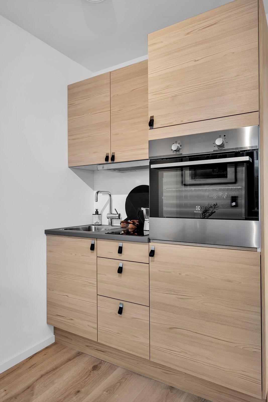 Oppgradert hybelkjøkken med integrerte hvitevarer.