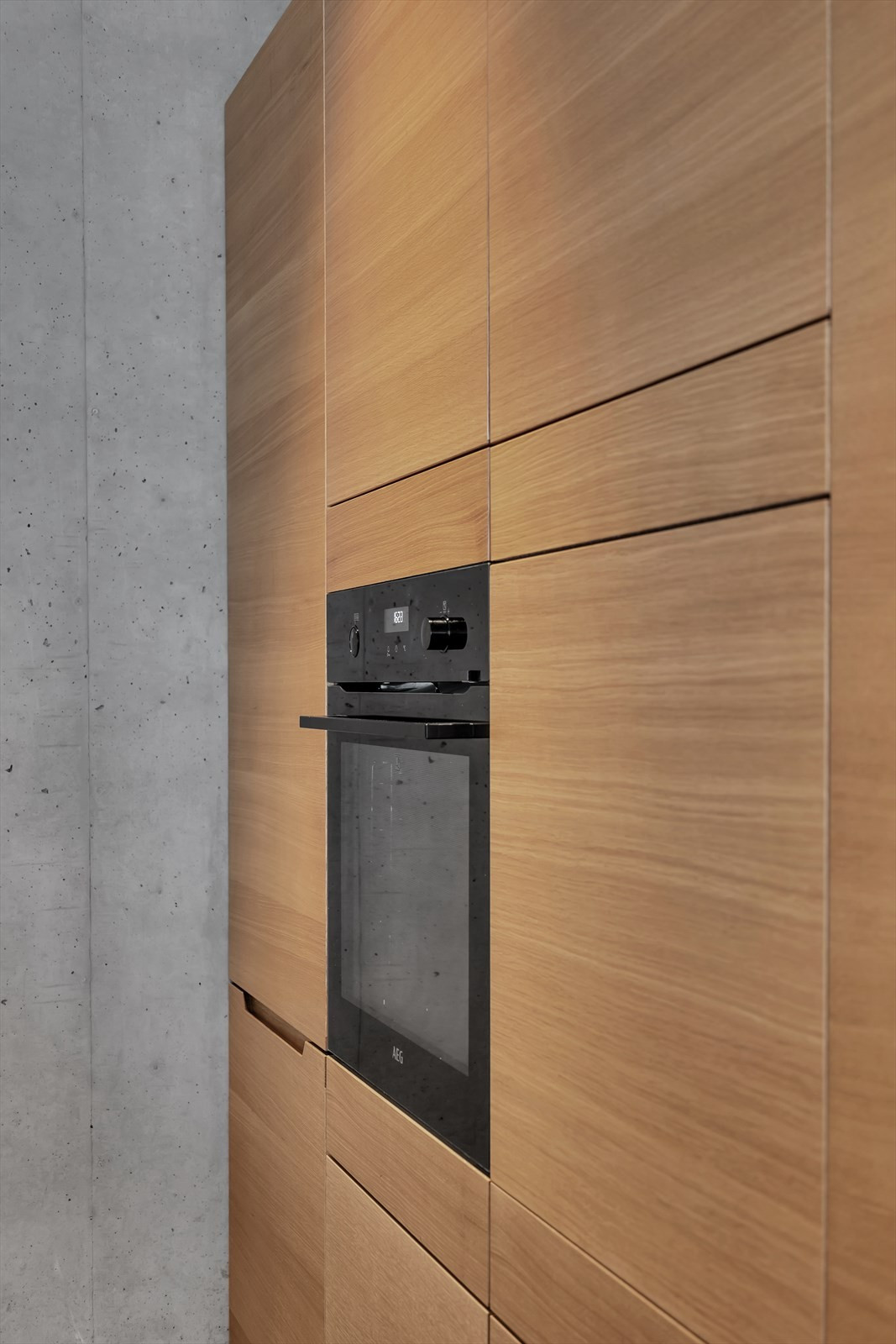 Integrert ovn, kjøleskap og fryseskap i en hel vegg med innredning.