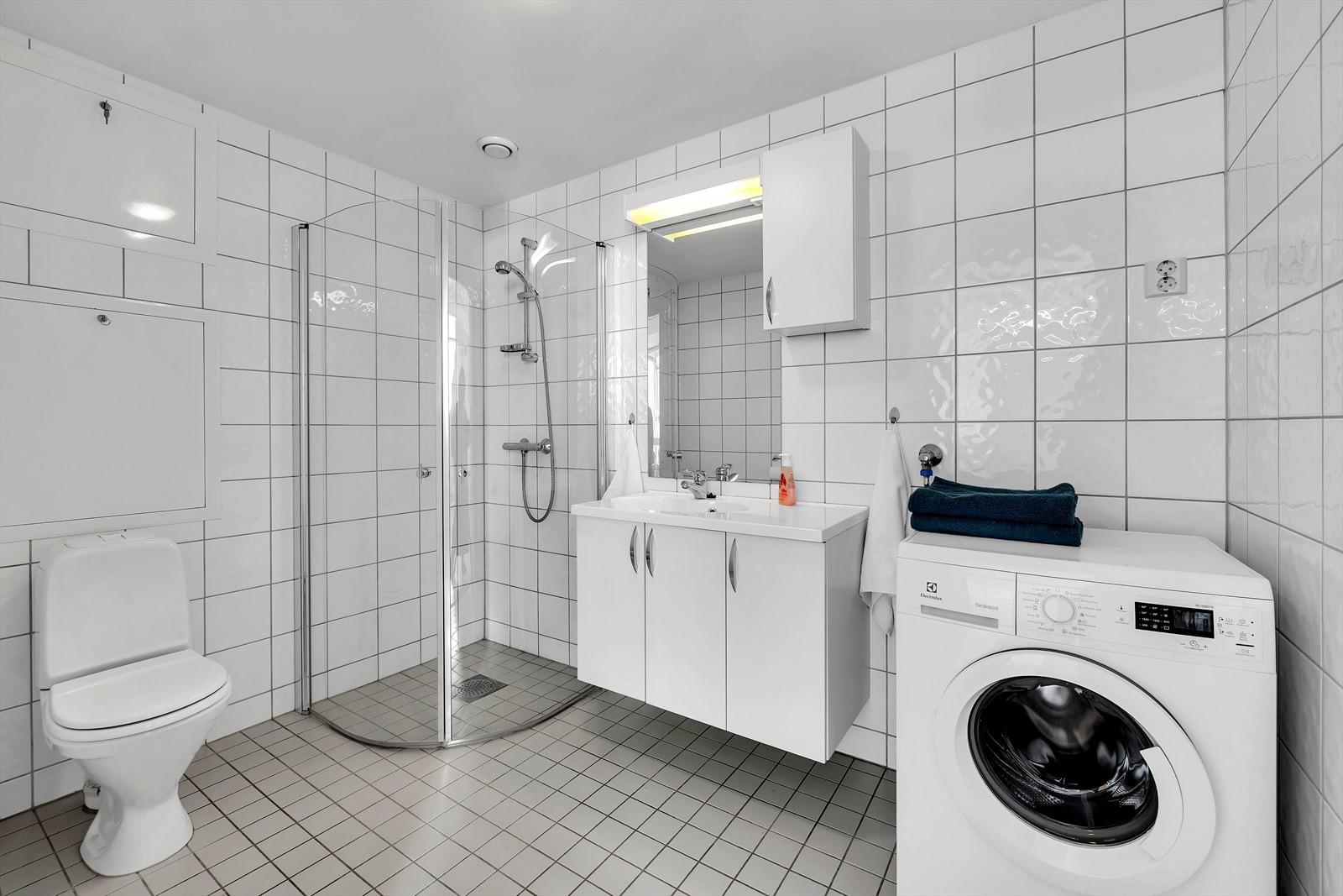 Flislagt badrom med dusjhjørne.