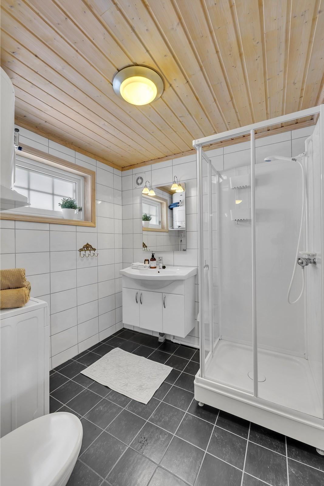 Badrom m/ dusjkabinett, toalett og opplegg til vaskemaskin.