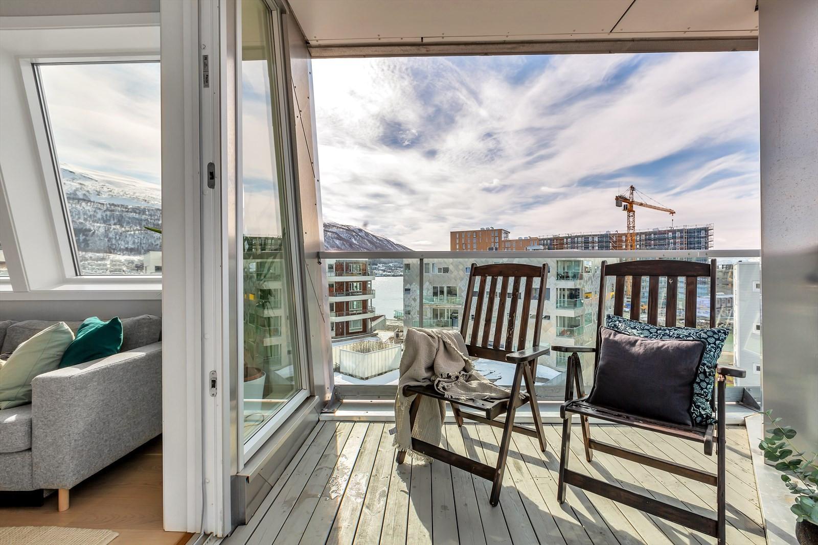 Balkong og stue. Takoverbygget og glassrekkverk.