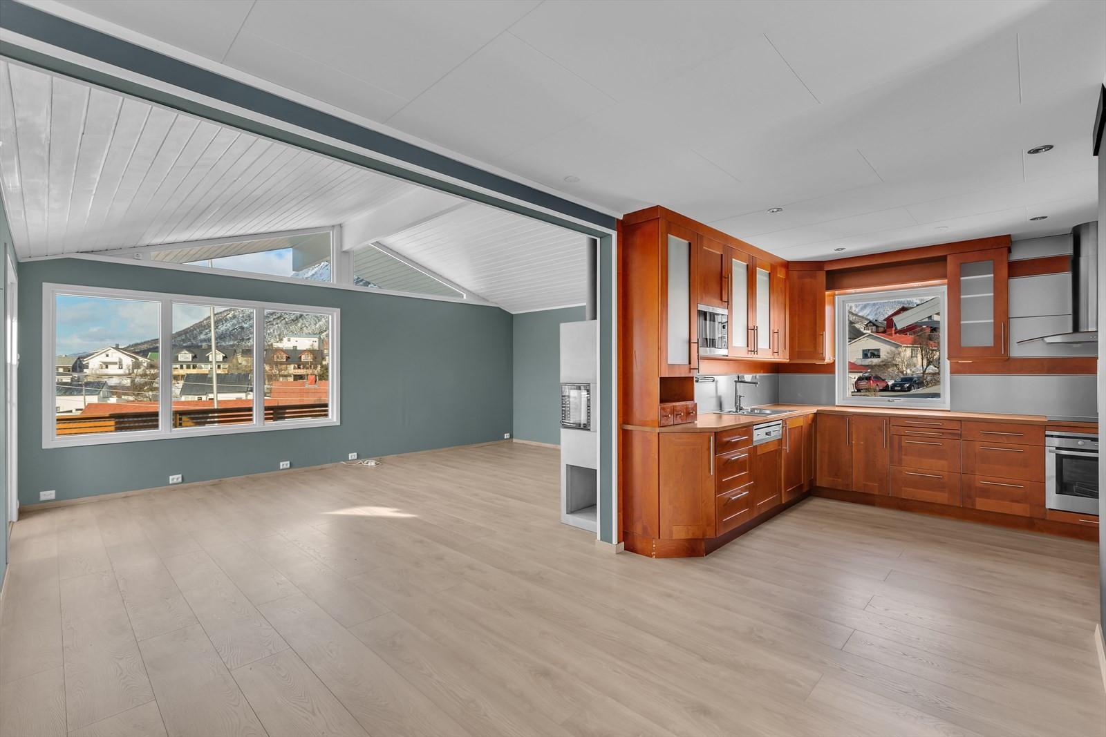 Åpen løsning med stue og kjøkken. Kjøkkenet er likevel skjult fra stuen.