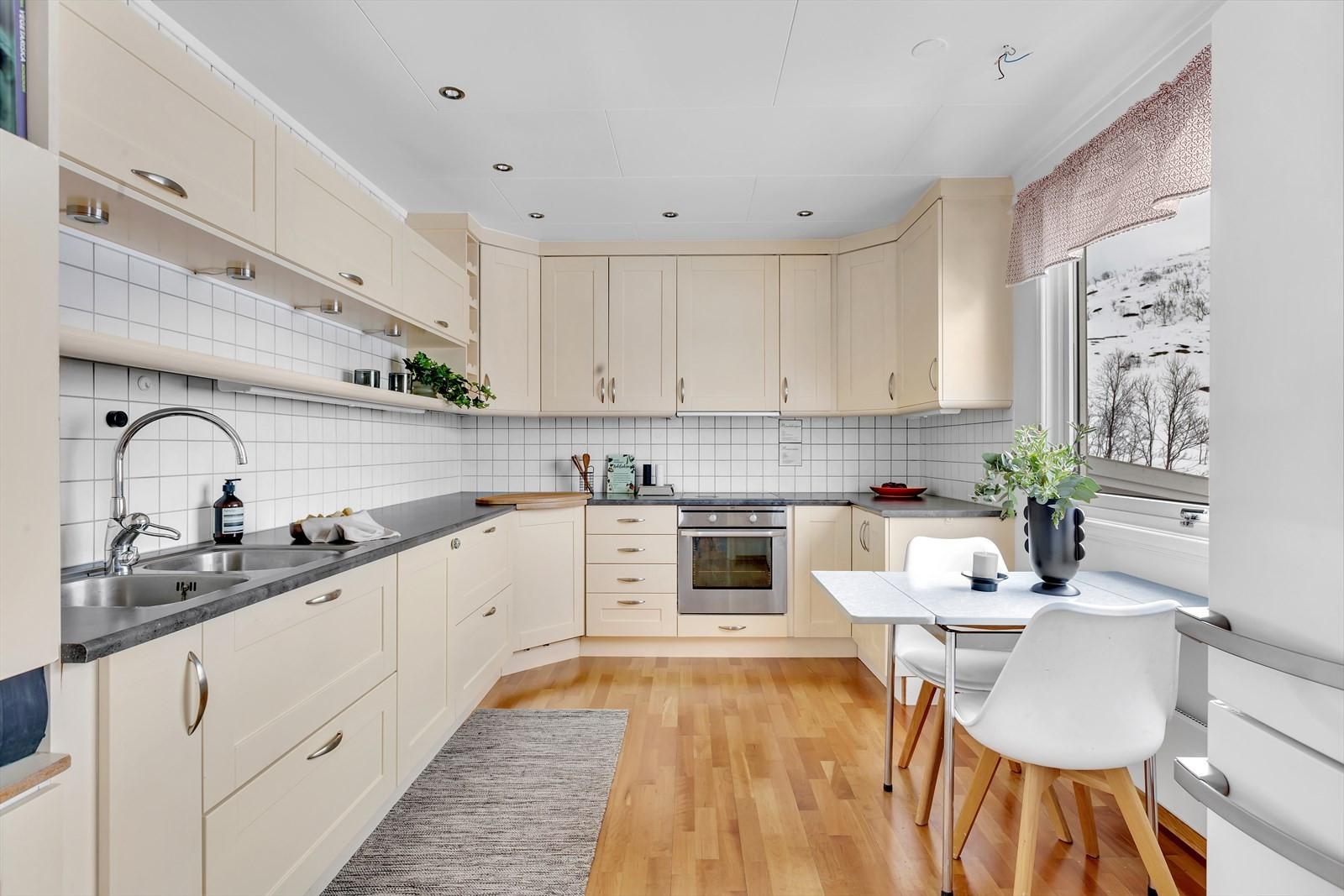 Kjøkken med integrert oppvaskmaskin, koketopp og stekeovn.