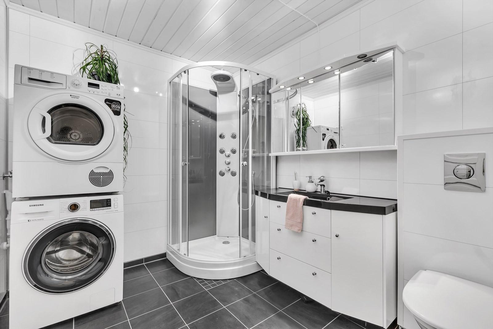 Lyst og trivelig badrom med flisgulv, varmekabler, vegghengt toalett.