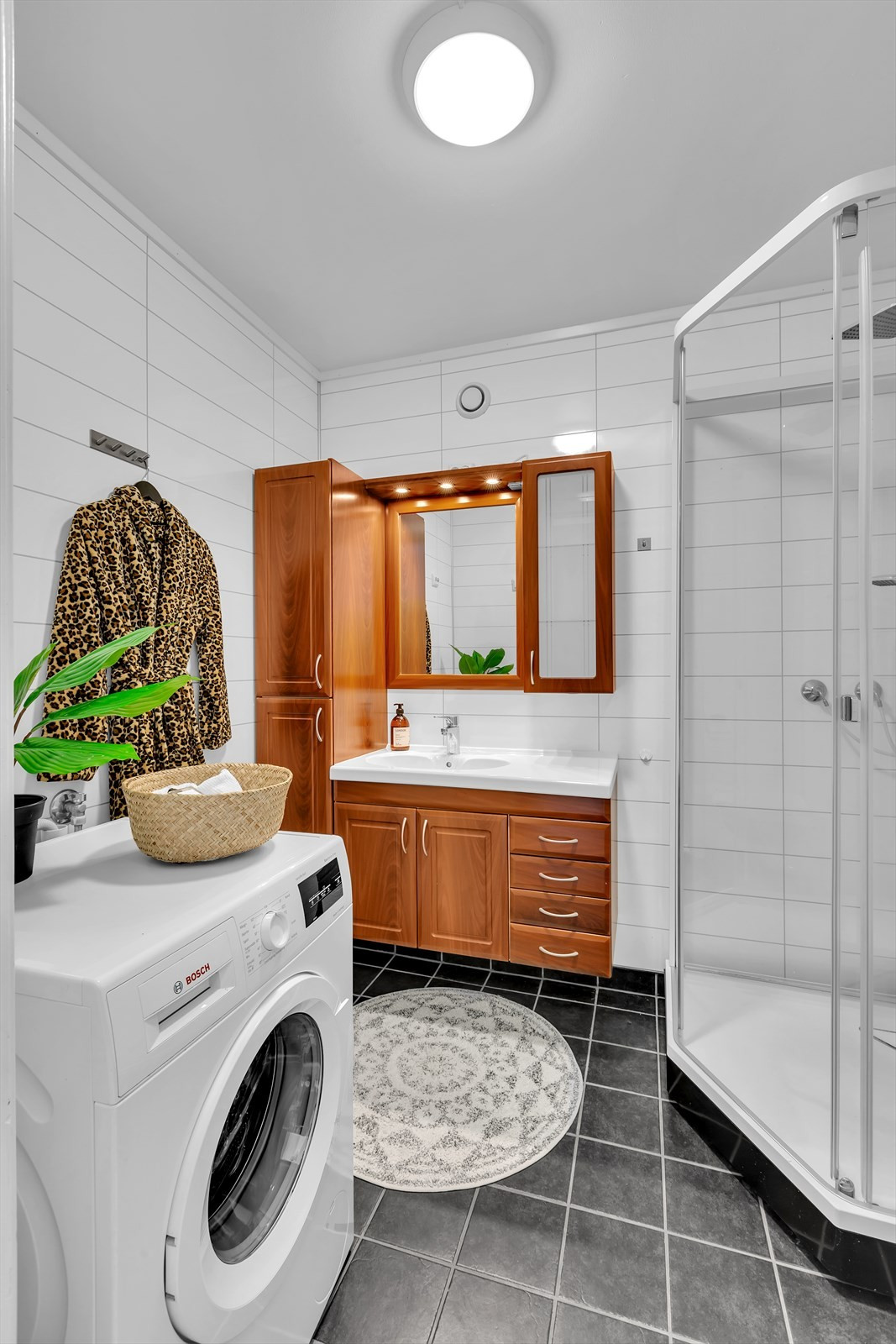 Flislagt badrom med dusjkabinett.