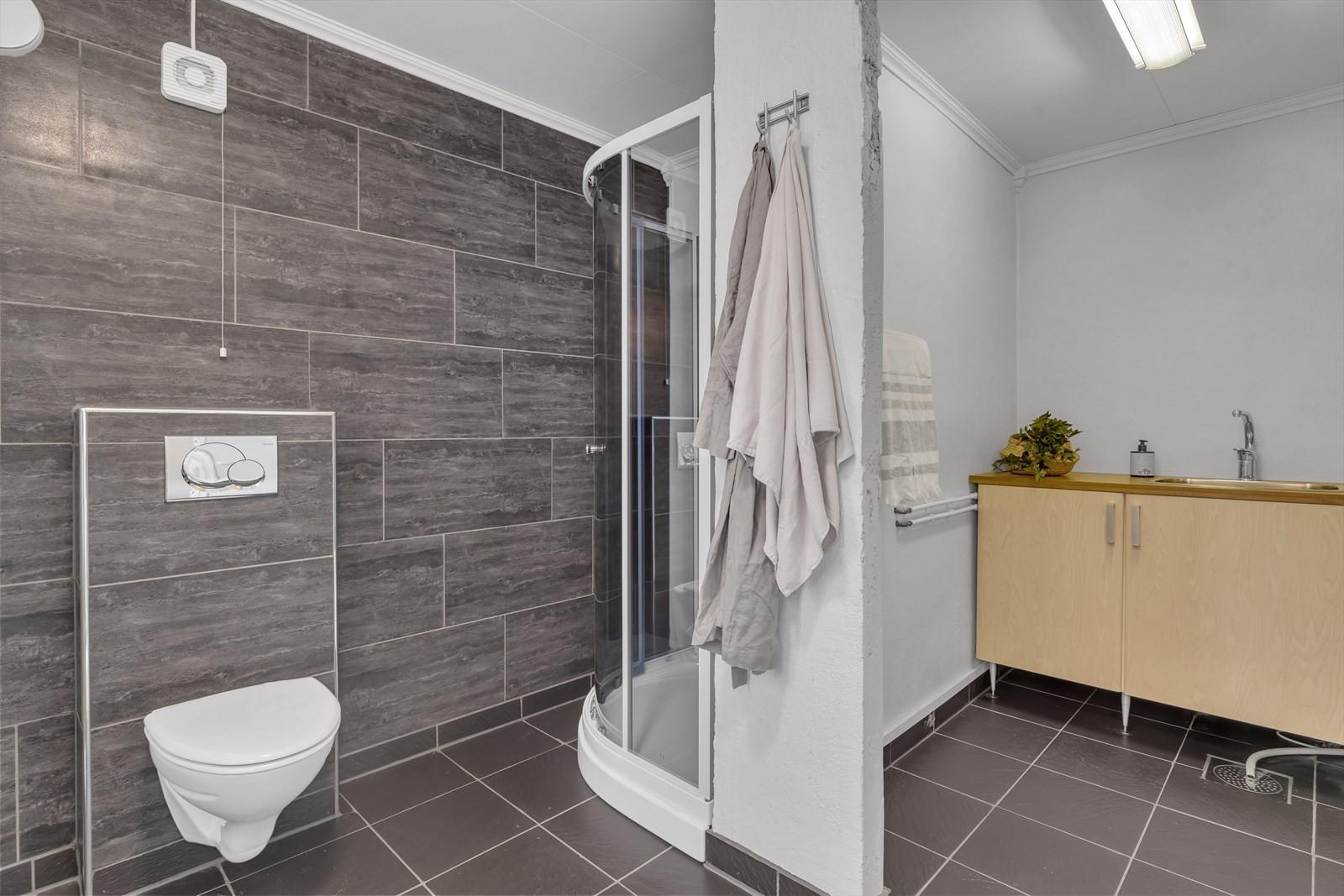 Romslig badrom med dusjkabinett og vegghengt toalett.