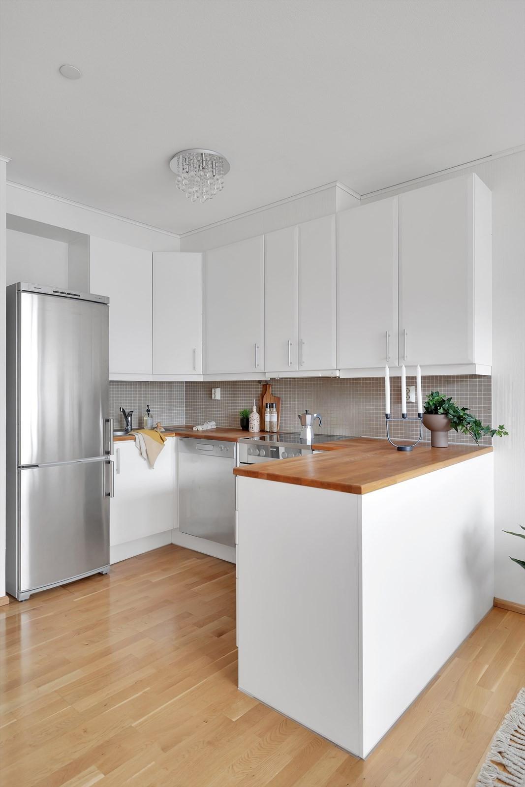 Lyst og tiltalende kjøkken med hvitevarer som følger med i handelen.