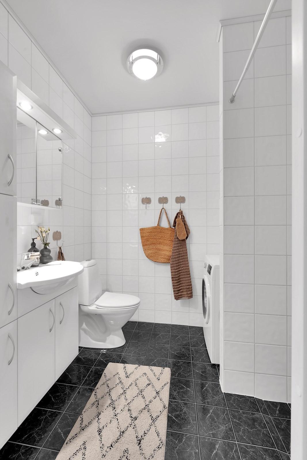 Boligen har ett flott flislagt bad med baderomsinnredning med over/underskap, wc, opplegg til vaskemaskin og dushjørne.