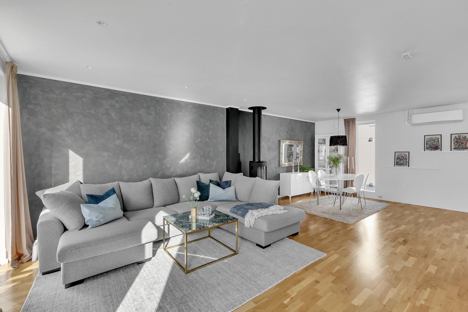 Romslig stue med god takhøyde, stor vindusflater og downlights.