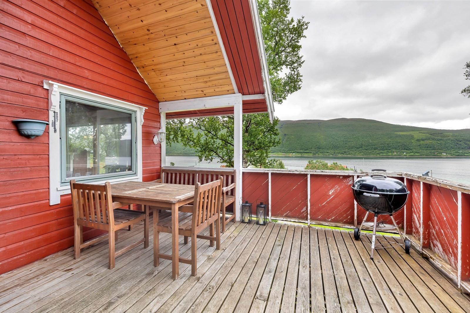 Stor hytte med terrasse foran inngangen.