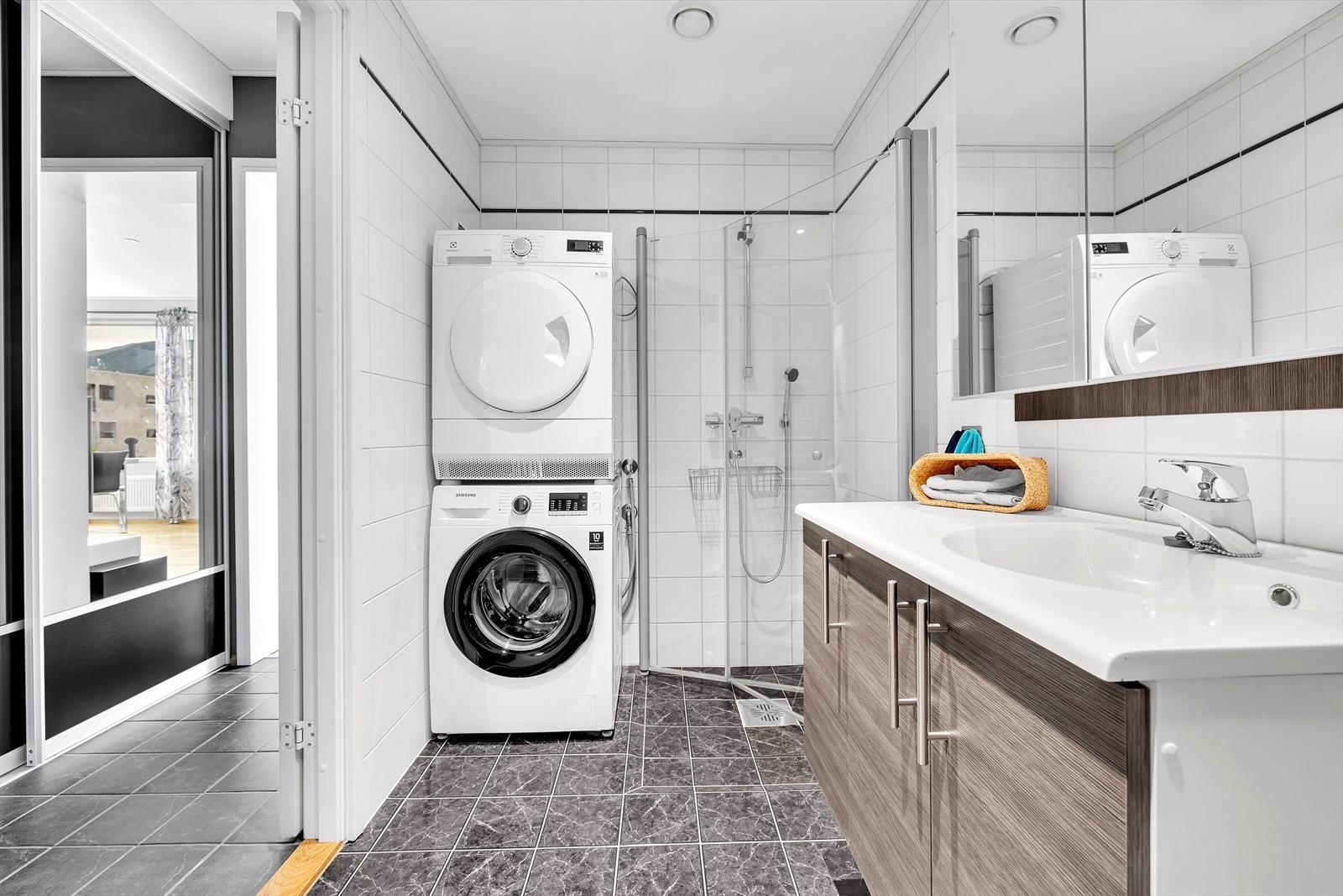 Flislagt bad med god skapplass og plass til vaskemaskin og trommel.