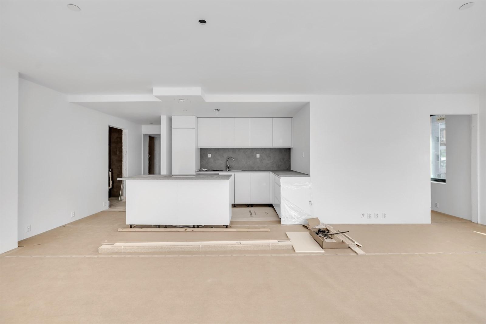 Åpen stue og kjøkken løsning, Hvit kjøkken fra Kvik med takhengt ventilator - ennå ikke montert. Benkeplate i grå laminat.