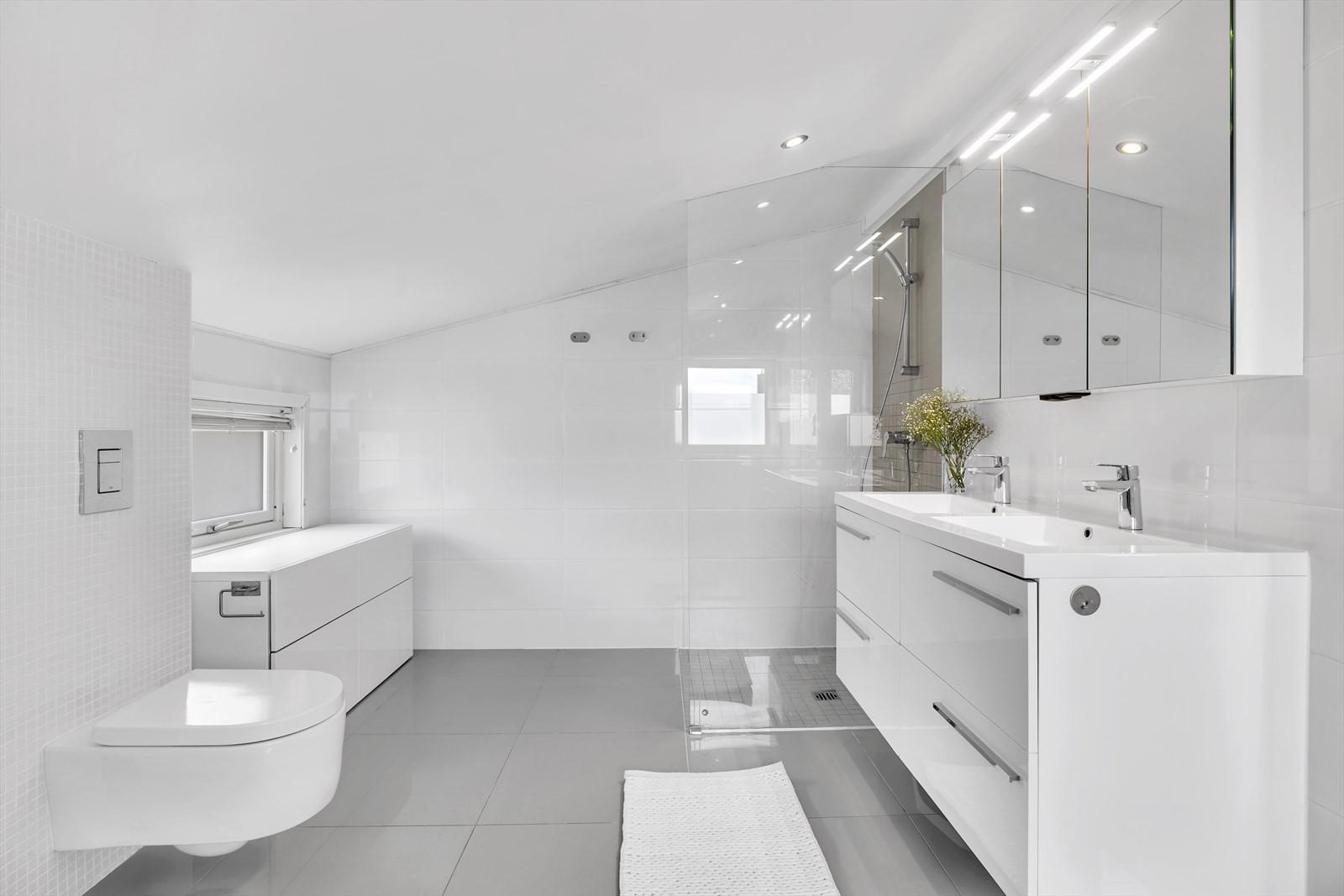 Fint rom med innredning med doble servanter, dusjnisje og hjørnekar