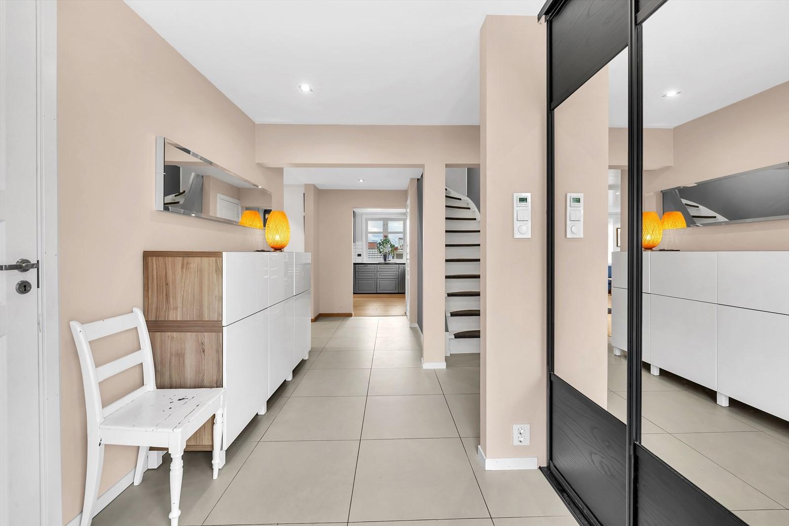 Velkommen inn! - Det første som møter deg i boligen er denne flotte ganger som har en fin skyvedørsgarderobe, storformat fliser på gulv og som leder deg til et praktisk bad/vaskerom og inn til stue / kjøkken
