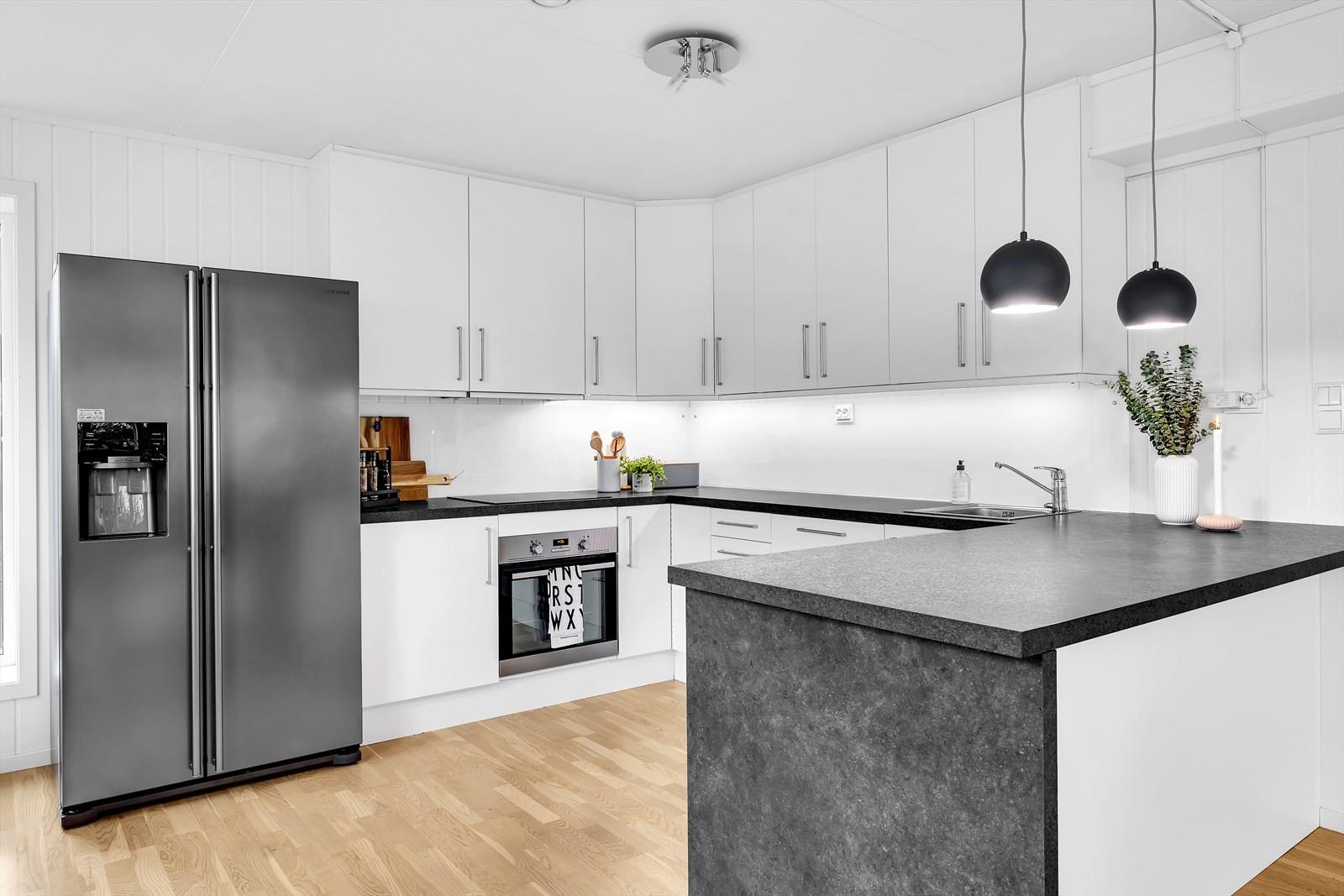 Moderne kjøkken med integrert stekeovn, koketopp og oppvaskmaskin