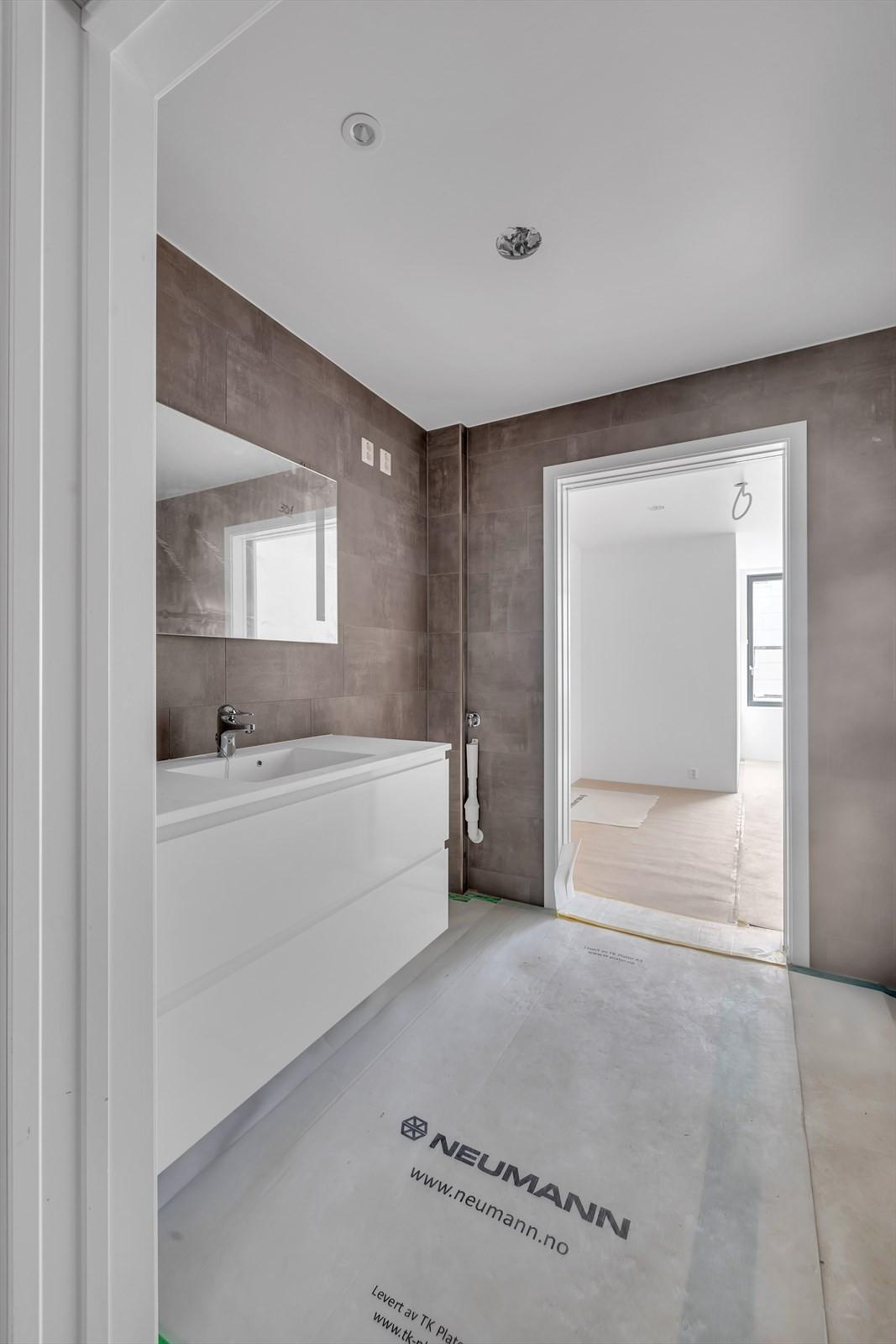Baderom med delikate fliser, vegghengt toalett, vask med hvitt underskap, speil med lys, dusj med sammen foldbare glassdører. Veggfliser i 60*40, gulvfliser, Gulvfliser i 60*60, i dusjnisje fliser i 10*10, Bad med direkte adkomst til hovedsoverom