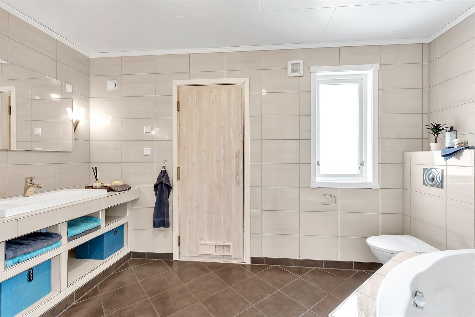 Flislagt bad med gulvvarme. Vegghengt WC. Stor baderomsinnredning. med god oppbevaringsplass.
