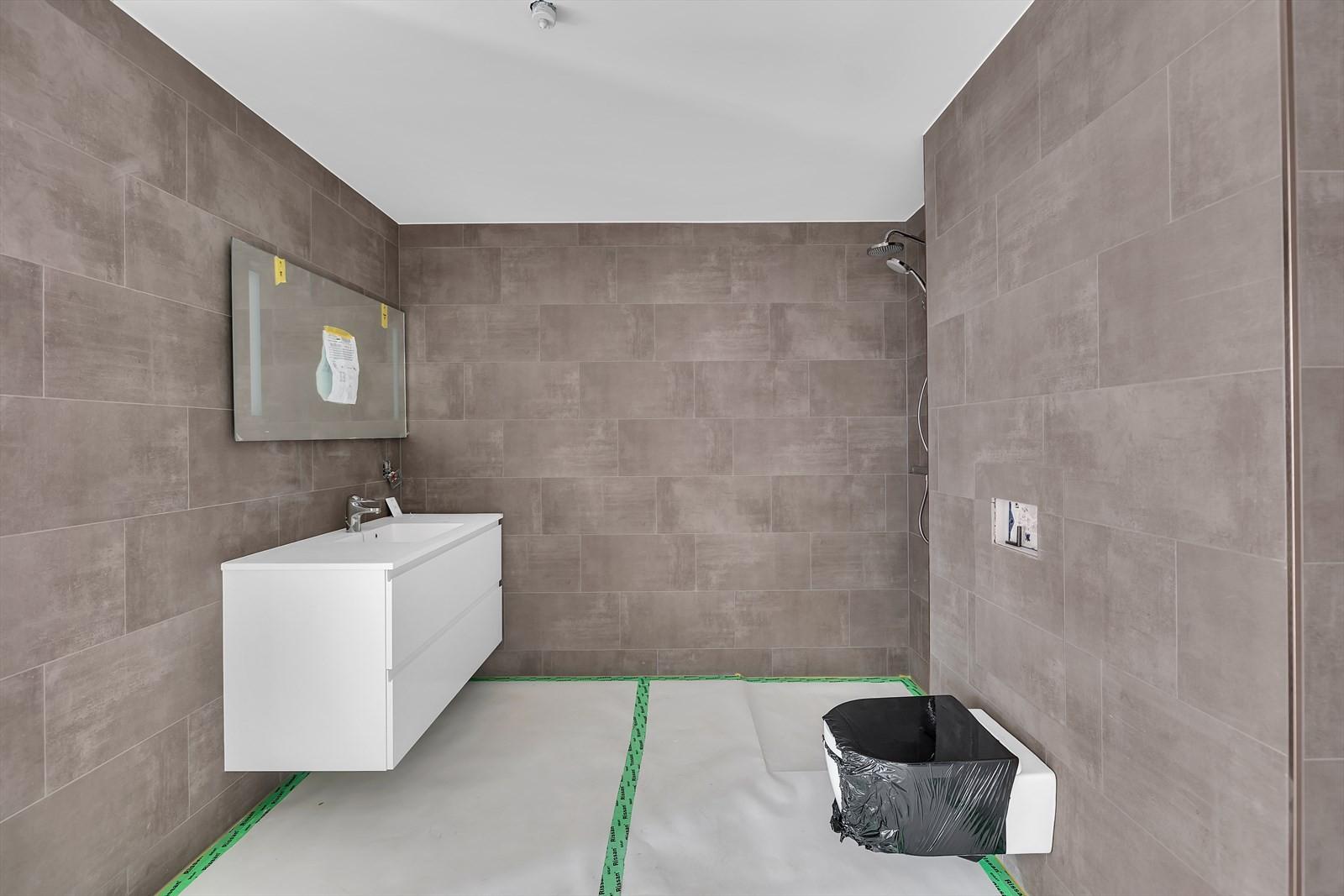 Baderom med delikate fliser, vegghengt toalett, vask med hvitt underskap, speil med lys, dusj med sammen foldbare glassdører. Veggfliser i 60*60, gulvfliser, Gulvfliser i 60*60, i dusjnisje fliser i 10*10