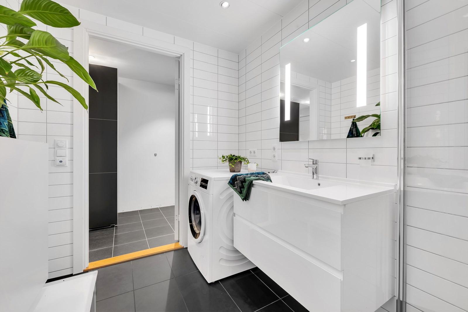 Baderom med delikate fliser, vegghengt toalett, vask med hvitt underskap, speil med lys, dusj med sammen foldbare glassdører.