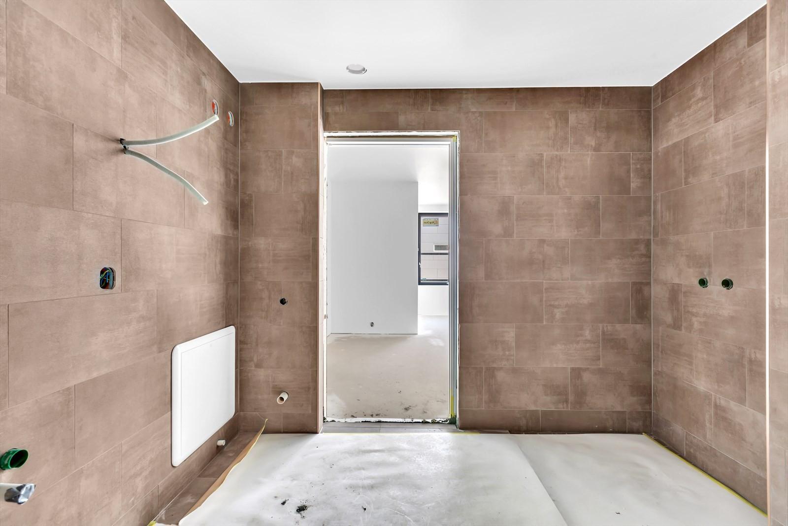Baderom med delikate fliser, vegghengt toalett, vask med hvitt underskap, speil med lys, dusj med sammen foldbare glassdører. Veggfliser i 60*40, gulvfliser, Gulvfliser i 60*60, i dusjnisje fliser i 10*10
