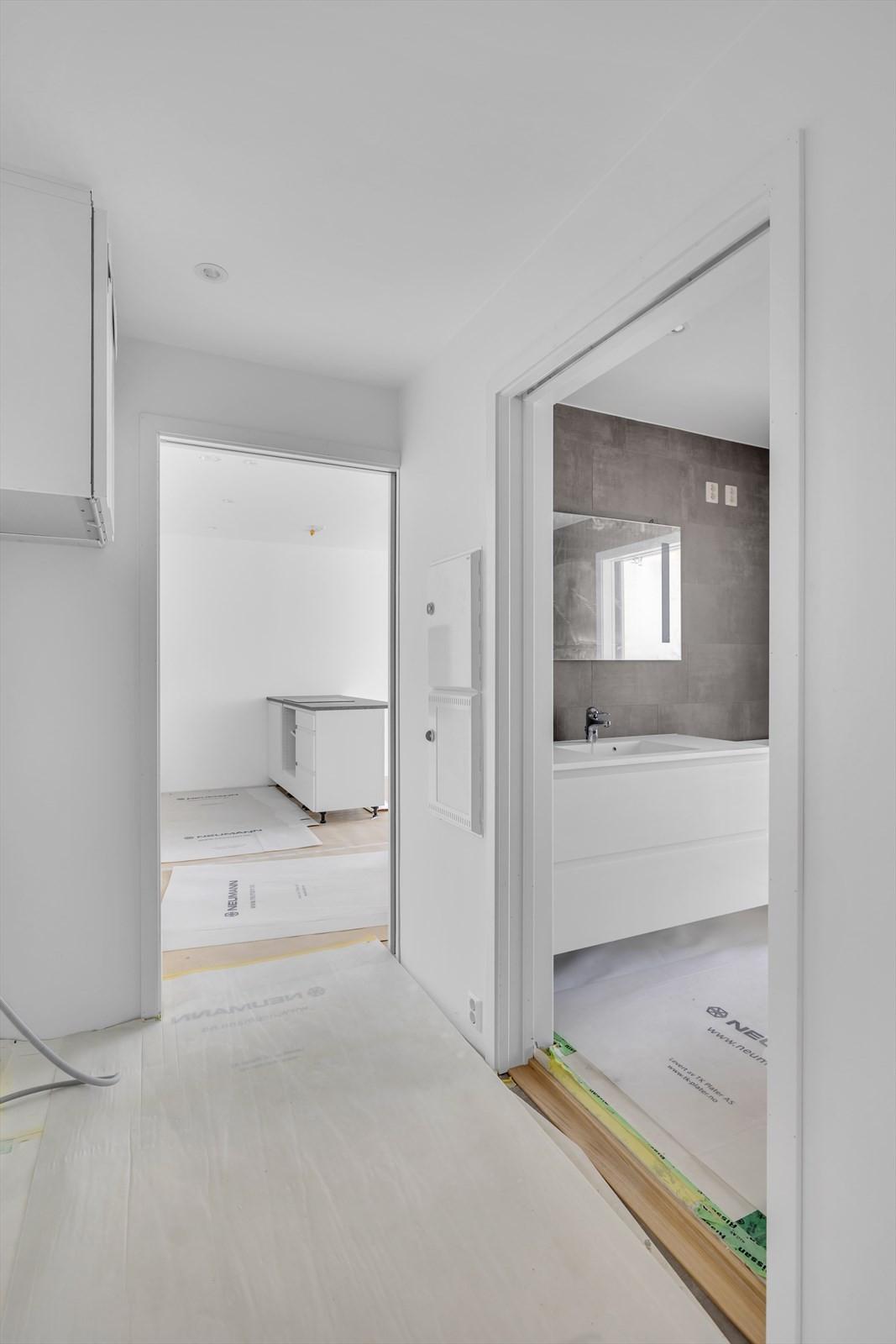 Gang med mot kjøkkenet - Badet til venstre med innredning fra Kvik - Vegghengt speil med lys