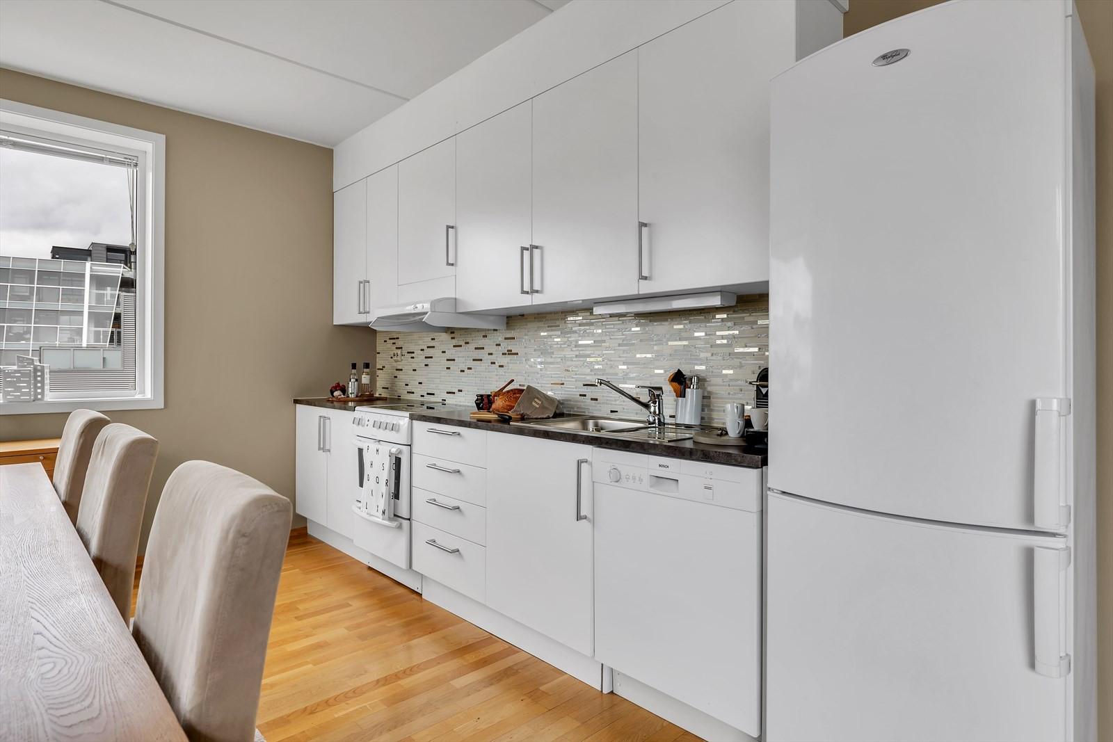 Kjøkkeninnredning med god oppbevaringsplass og fliser over benk.