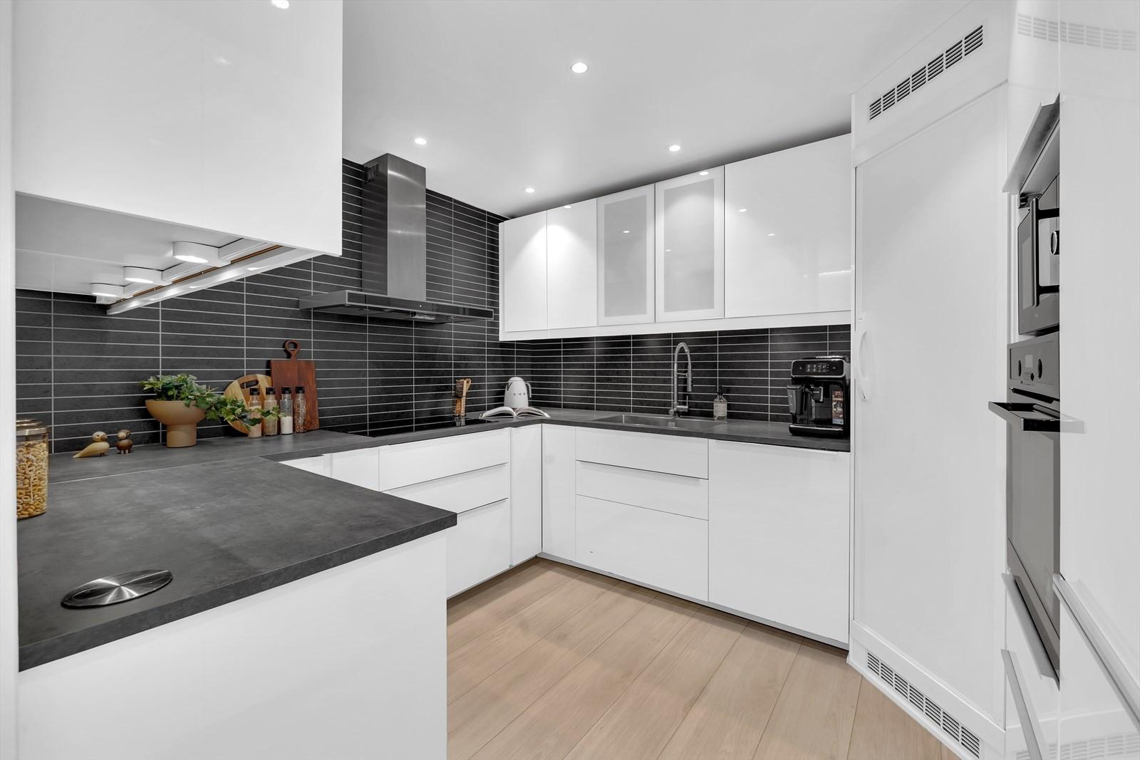 Kjøkken med moderne innredninger og integrerte hvitevarer.