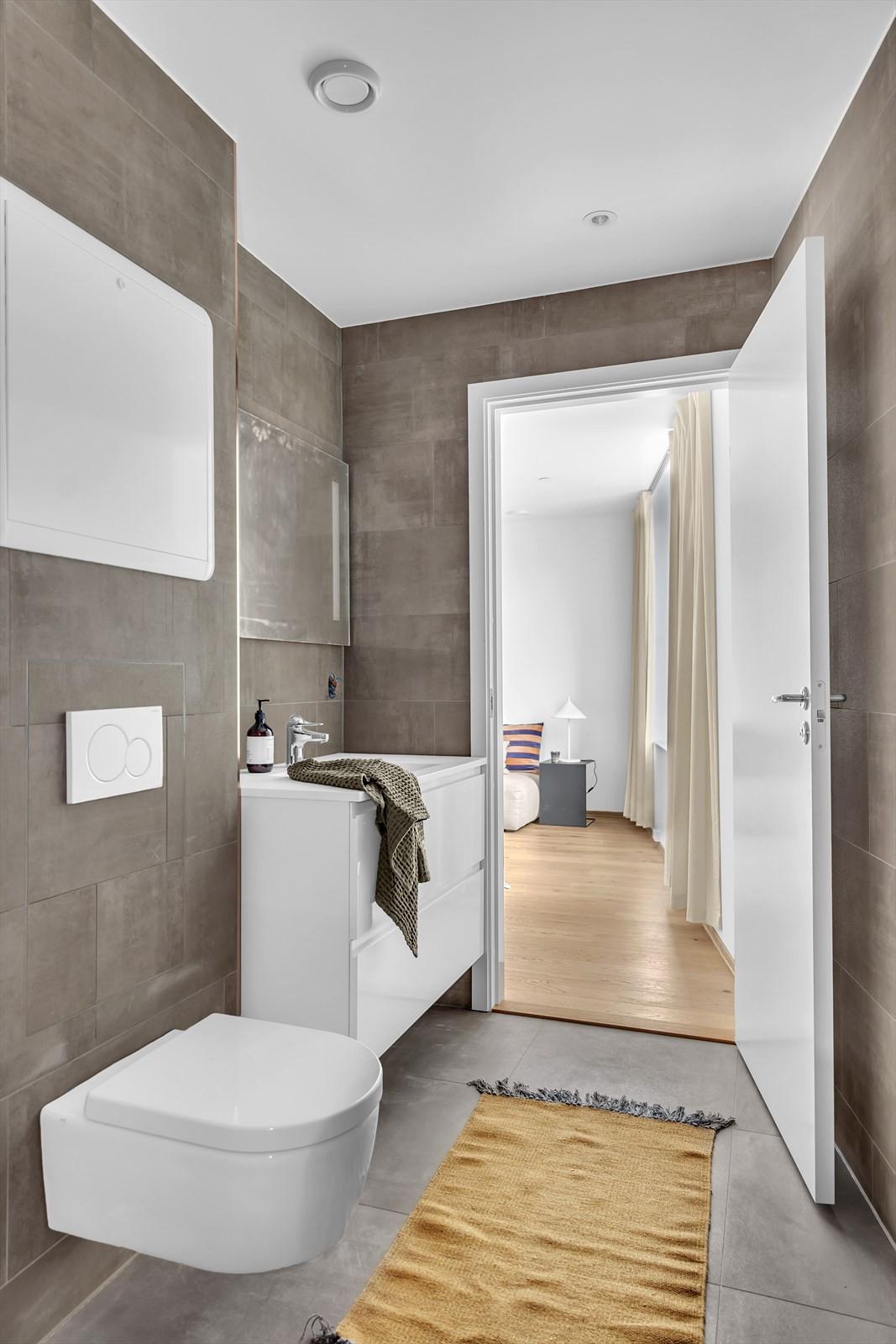 Lekkert baderom med flislagte gulv og vegger lik leilighetene ellers i prosjektet