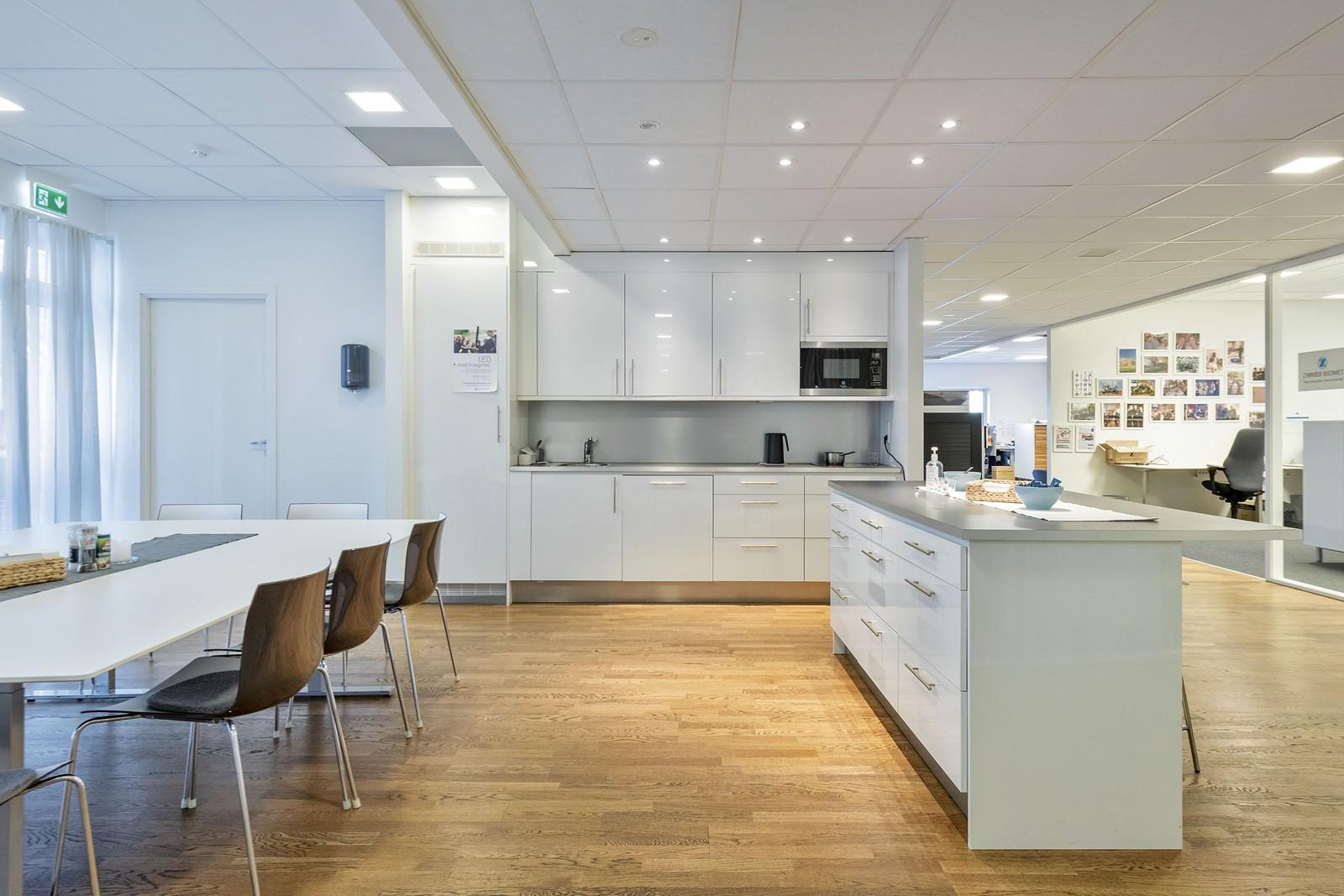 Innholdsrikt kjøkken med kjøleskap, koketopp, mikroovn og oppvaskmaskin