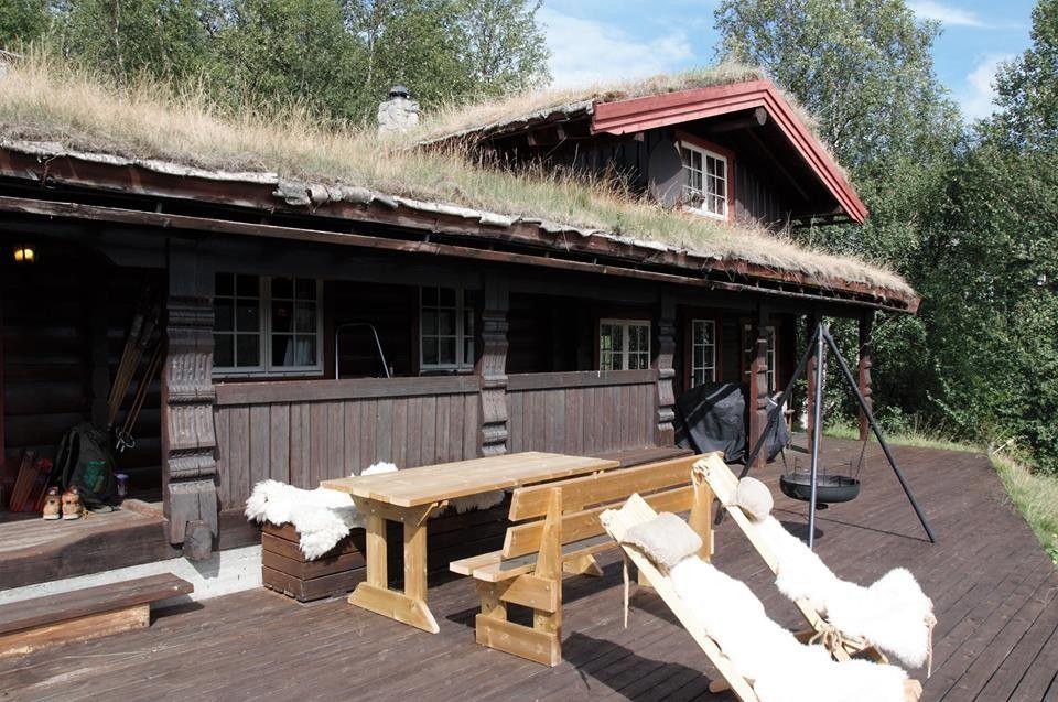 Hyggelig tømmerhytte med gress på taket.